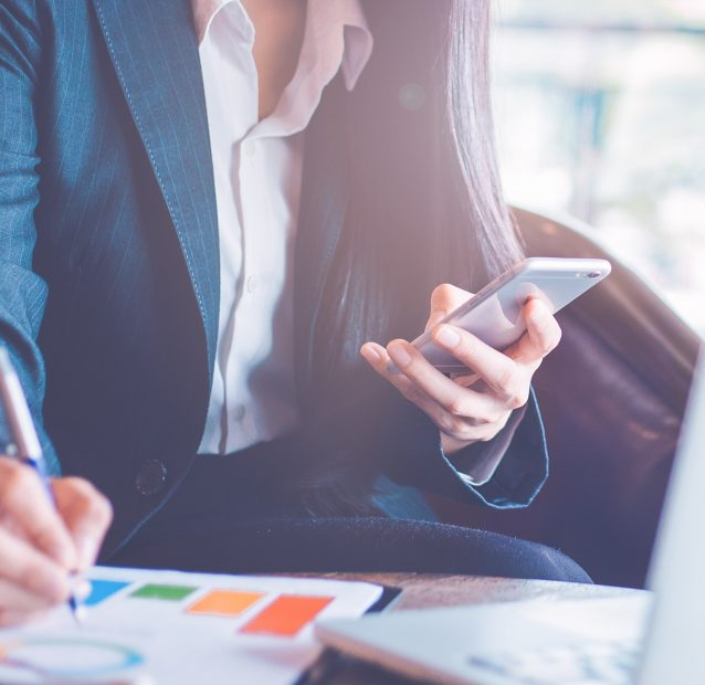 Business  woman uses a smartphone and writing on charts and graphs that show results.Web banner.